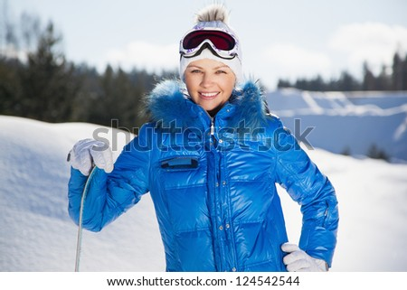 Pretty young woman standing with snowboard in her hand, sunny winter day