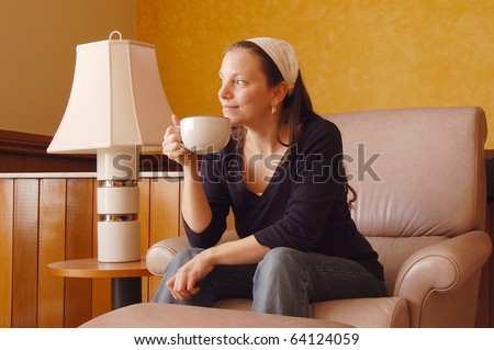 Pretty Young Woman Staring Dreamily on a Recliner while Sipping Coffee - stock photo