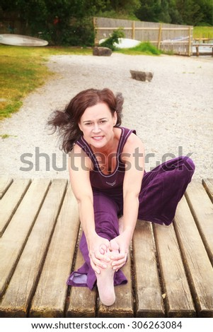 Pretty young woman stretching her muscles as she works out sitting on a wooden jetty on a river or lake looking up at the camera with a lovely smile