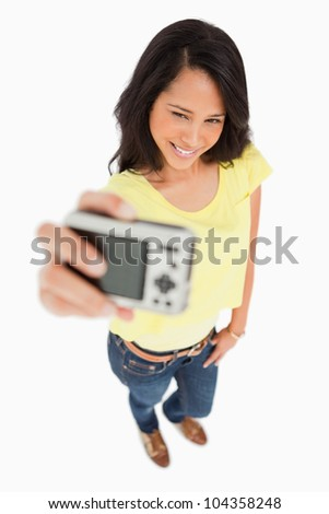 Pretty young woman taking a picture of herself against white background
