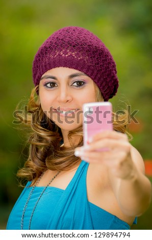 Pretty young woman taking pictures from her cell phone - stock photo