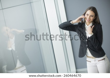 Pretty young woman talking on the phone in office - stock photo