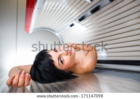 Pretty young woman tanning her skin in a modern solarium - stock photo