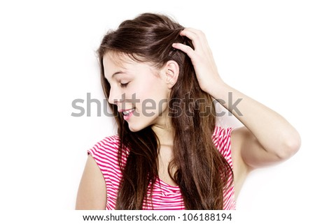 pretty young woman touching her hair and looking sideways - isolated against white background - stock photo