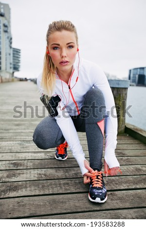 Pretty young woman tying her shoe laces before a run. Fit young female runner training outdoors. - stock photo