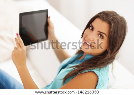 Pretty young woman using digital tablet at home - stock photo