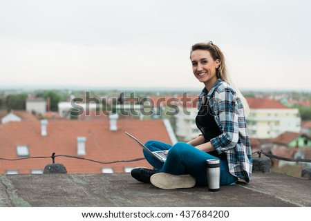 Pretty young woman using her laptop on the roof. Chilling. Looking at camera. - stock photo