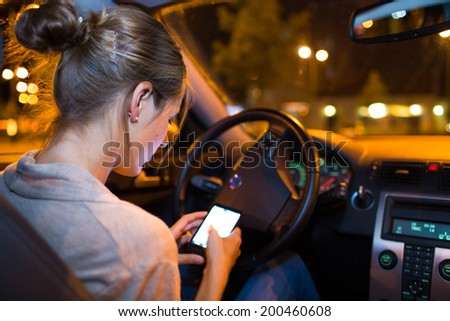 Pretty young woman using her smart phone while driving her car at night - stock photo