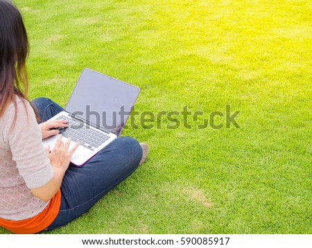 Pretty Young woman using laptop computer. Female working on laptop in an outdoor green grass field
