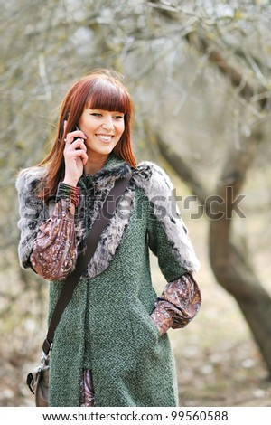 Pretty young woman using mobile phone outdoors - stock photo