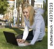 Pretty young woman using wireless laptop outdoors on college campus. - stock photo