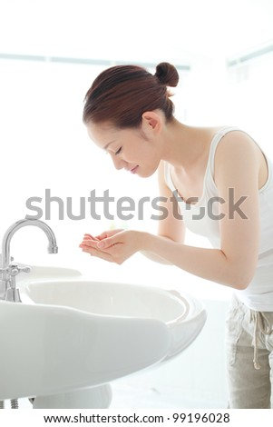 Pretty young woman washing her face at a wash basin - stock photo