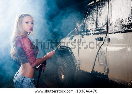 Pretty young woman washing offroad car by foam hose - stock photo