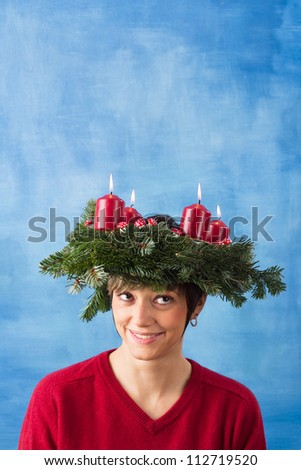Pretty young woman wearing advent wreath on her head, four candles are burning. Studio shot with copy space against a blue background, series. - stock photo
