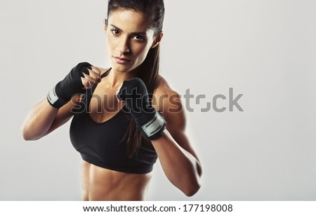 Pretty young woman wearing boxing gloves posing in combat stance looking at camera. Fit young female boxer ready for fight on grey background - stock photo