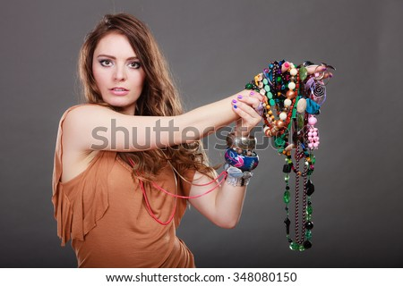 Pretty young woman wearing bracelets and rings holding many plentiful of precious jewelry necklaces beads. Portrait of gorgeous fashion girl in studio on gray. - stock photo