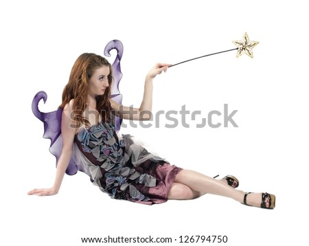 Pretty young woman wearing fairy costume and holding magic wand - stock photo