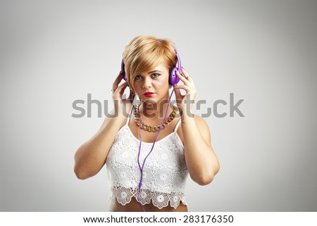Pretty young woman wearing purple headphones listening to music