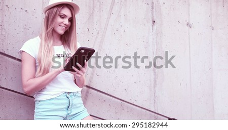 Pretty Young Woman Wearing Trendy Outfit, Using her Tablet Computer While Leaning Against the Building Wall - stock photo