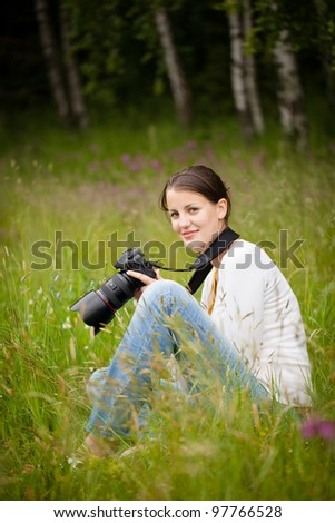 pretty young woman with a DSLR camera outdoors, taking pictures - stock photo