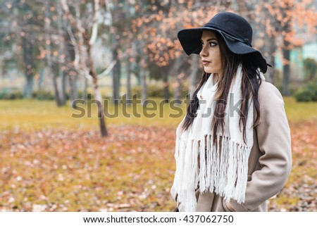 Pretty young woman with a hat at autumn park