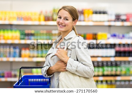 Pretty, young woman with a shopping basket buying groceries in a supermarket/mall/gr ocery store (color toned image; shallow DOF) - stock photo