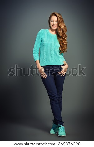 Pretty young woman with beautiful curly hair. Knitted clothes. Seasonal style. Full length portrait.