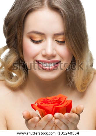 Pretty young woman with beautiful fresh make-up and perfect healthy skin holding rose in her hands - stock photo