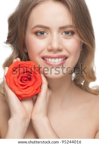 Pretty young woman with beautiful make-up and blond curly hair with rose in her hands - stock photo