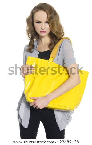Pretty young woman with big yellow bag standing posing - stock photo