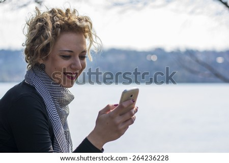 Pretty young woman with blond curly hair typing on the phone sitting on the root of the big tree near the river.She is smiling as she is communicating with her friends via social networks. - stock photo