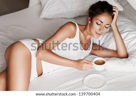 pretty young woman with cup of tea in white bed - stock photo