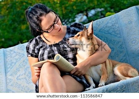 pretty young woman with dog reading magazine