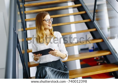 Pretty young woman with glasses working with digital tablet in the office