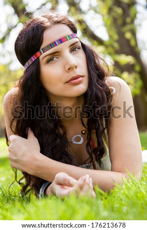 Pretty young woman with her beautiful long wavy brunette hair in a headband lying on the fresh green summer grass daydreaming in the sunshine with a faraway expression - stock photo