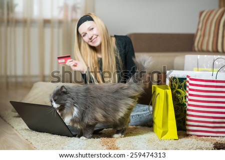 Pretty young woman with her cat making online shopping at home.