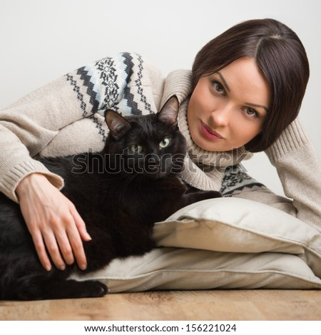 Pretty young woman with her cat on the floor at home - stock photo