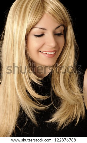 Pretty young woman with layered honey blond hairstyle, smiling