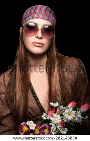 Pretty Young Woman with Long Straight Brown Hair, Wearing Boho Fashion in Hippie Style and Holding a Bouquet of Flowers. Portrait isolated on Black Background. - stock photo