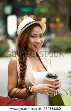 Pretty young woman with paper bags and coffee and looking at the camera