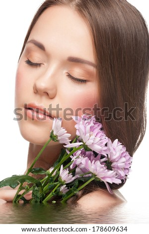 Pretty young woman with perfect healthy skin with flowers in water. Beauty treatment concept