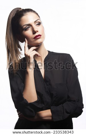 Pretty young woman with ponytail and red lipstick and make up, with finger on her cheek, in black shirt, thinking. Isolated on white background.