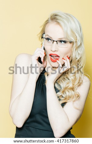 Pretty young woman with red lipstick and long blond curly hair wearing glasses and black dress holding mobile phone on yellow background
