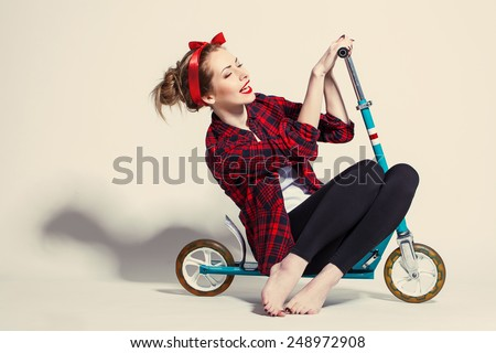 Pretty young woman with scooter - stock photo