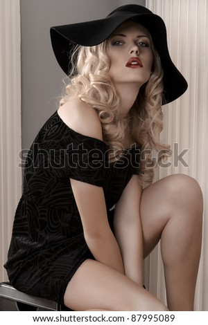 pretty young woman with sensual red lips dressed with a black dress and a huge hat - stock photo