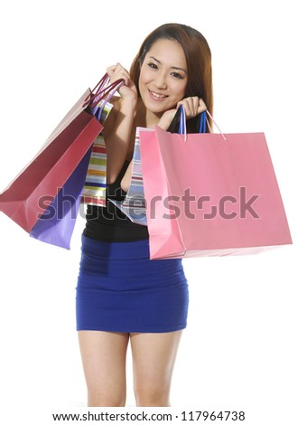 Pretty young woman with shopping colorful bag posing