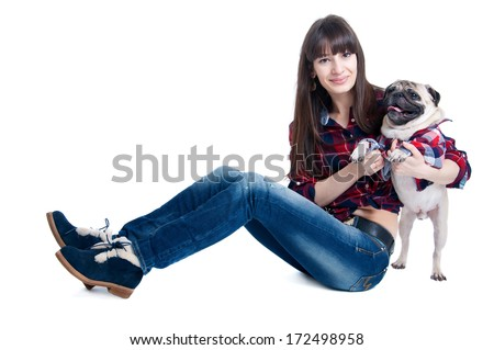 Pretty young woman with straight hair and long legs, sitting and playing together with her friend pug dog pet, both wearing squared pattern shirts, both looking at camera. Isolated on white background - stock photo