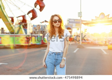 Pretty young woman with sunglasses in a white shirt and vintage jeans walking in the amusement park at beautiful sunset