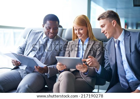 Pretty young woman with touchpad and her two male colleagues discussing data in airport - stock photo