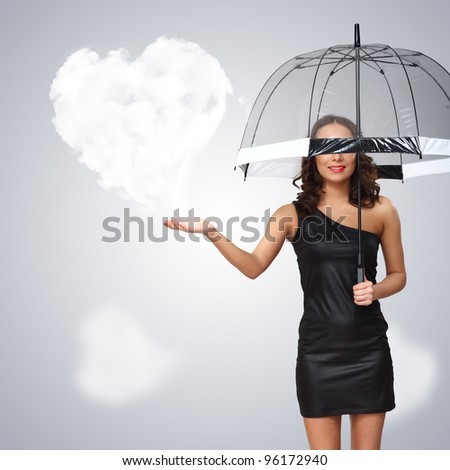 Pretty young woman with umbrella and with hearts on the background